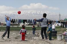 """Дети играют в лагере беженцев в Ливане 15 марта 2015 года. Великобритания примет """"еще тысячи"""" сирийских беженцев, заявил в пятницу премьер-министр Дэвид Кэмерон, изменив позицию после того, как всплеск эмоций общественности, вызванный изображением мертвого сирийского ребенка на турецком пляже, заставил его действовать.  REUTERS/Jamal Saidi"""
