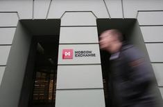 Мужчина проходит мимо здания Московской биржи 7 ноября 2014 года. Российский фондовый рынок завершает неделю снижением, расценив данные об увеличении числа рабочих мест и уровне безработицы в США за август как сигнал о неминуемом повышении процентных ставок ФРС уже в сентябре REUTERS/Maxim Shemetov