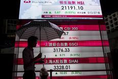 Un hombre camina frente a unas pantallas que muestran el desempeño de los principales índices bursátiles de China en el distrito financiero de Hong Kong.  REUTERS/Tyrone Siu