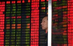 Un inversor frente a un tablero electrónico que muestra la información de las acciones en una correduría en Shanghái, China, 2 de septiembre de 2015. Los intentos de las autoridades y los reguladores chinos para calmar a los inversores nerviosos con promesas de reformas a los mercados financieros y garantías de que la economía se está estabilizando tuvieron un impacto limitado el lunes, cuando las acciones cerraron a la baja. REUTERS/China Daily