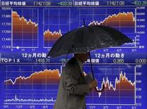 Un hombre camina junto a un tablero electrónico que muestra la gráfica del índice Nikkei de Japón, afuera de una correduría en Tokio, 8 de septiembre de 2015. Las bolsas de Asia subían el martes tras una racha de seis días de pérdidas y el dólar se fortalecía frente al yen japonés, pero las ganancias eran limitadas luego de que una caída en las importaciones chinas aumentó el temor a una desaceleración más severa en la segunda economía más grande del mundo. REUTERS/Issei Kato