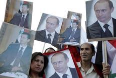 Сторонники президента Сирии Башара Асада с его потретами и портретами президента России Владимира Путина у посольства России в Дамаске 7 мая 2012 года. Отказываясь сообщать о масштабах своего военного присутствия в Сирии, Россия заставляет Запад опасаться серьезного наращивания такового и надеется набрать очков в переговорах с мировыми державами, говорят западные дипломаты. REUTERS/Khaled al- Hariri