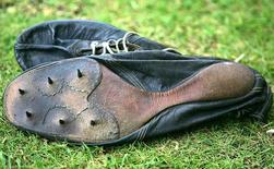 The running shoes used by Britain's Sir Roger Bannister when he ran the first sub-four-minute mile in 1954 lie on the grass at Pembroke College, Oxford, during celebrations for the 50th anniversary of the event, May 6, 2004.  REUTERS/David Bebber