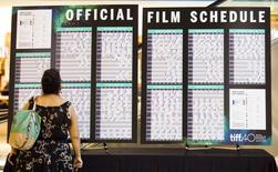 A woman looks at a film schedule before the opening night at the 40th Toronto International Film Festival in Toronto, Canada, September 10, 2015. TIFF runs from September 10-20.   REUTERS/Mark Blinch