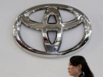 A woman walks under a logo of Toyota Motor Corp at the company's showroom in Tokyo, Japan, in this August 4, 2015 file photo. REUTERS/Yuya Shino