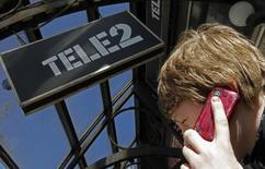 Мужчина говорит по телефону у салона Tele2 в Санкт-Петербурге. 28 марта 2013 года. Мобильный оператор Tele2 Россия сообщил в пятницу, что начнет предоставлять услуги в Москве и Московской области с 22 октября 2015 года, став четвертым федеральным игроком на высококонкурентном столичном рынке. REUTERS/Alexander Demianchuk