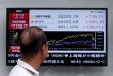 Un peatón mira un tablero electrónico que muestra la gráfica de fluctuación del índice Nikkei, el Dow Jones y el NASDAQ, afuera de una correduría en Tokio, Japón, 9 de septiembre de 2015. El índice Nikkei de la bolsa de Tokio subió el martes luego de que la reunión de política monetaria del Banco de Japón concluyó sin ninguna decisión sorpresiva. REUTERS/Yuya Shino