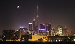 The moon turns orange during a total lunar eclipse behind the CN Tower and the skyline during moonset in Toronto October 8, 2014.  REUTERS/Mark Blinch