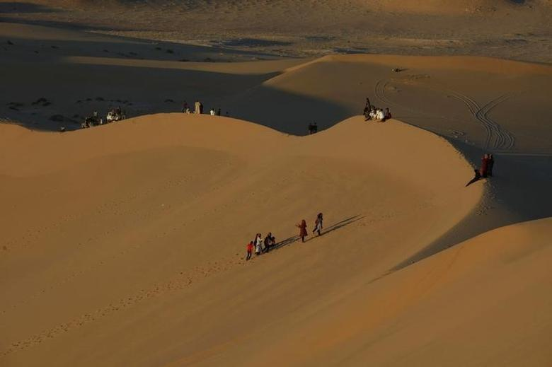 Residents walk on sand dunes in the Libyan desert oasis town of Ghadames April 19, 2013.  REUTERS/Ismail Zitouny