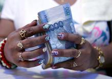 A casino financier, wearing rings and with painted fingernails, counts money she collected from a gambler moments before, in Angeles city, north of Manila, Philippines, in this May 25, 2015 file photo.  REUTERS/Erik De Castro/Files