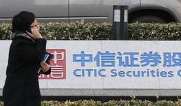 Una mujer camina junto a un letreto de Citic Securietes, en su oficina central en Pekín, 27 de marzo de 2013. Las acciones de CITIC Securities, la mayor correduría de China, cayeron el miércoles después que la firma dijo que algunos ejecutivos están bajo investigación policial, como parte de una pesquisa sobre una posible manipulación ligada a la caída de los mercados de valores chinos. REUTERS/Kim Kyung-Hoon