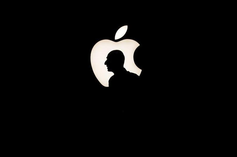 A man walks past a backlit Apple logo during an Apple media event in San Francisco, California, September 9, 2015. REUTERS/Beck Diefenbach