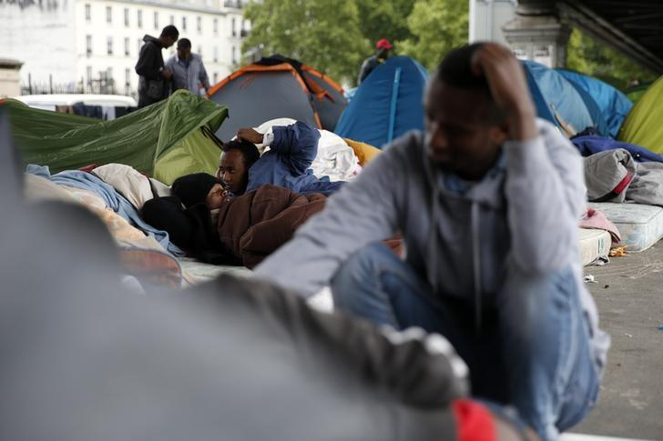 Migrants from Eritrea sit near tents as they live in a make-shift camp under a metro bridge in Paris, France, May 28, 2015.   . REUTERS/Benoit Tessier
