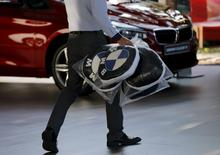 A dealer carries BMW's promotional cushions at a dealer shop in Beijing, China, September 11, 2015. REUTERS/Kim Kyung-Hoon