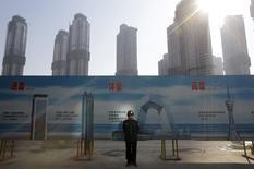 Un guardia de seguridad junto a un cartel publicitario detrás de un complejo residencial en construcción en Wuhan en enero de 2014. Los precios de las viviendas en China aumentaron por cuarto mes consecutivo en agosto, ofreciendo esperanza de que el debilitado sector inmobiliario es cada vez menos un lastre para la economía ralentizada. REUTERS/Stringer/Files