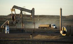 Un camión pasa junto a una unidad de bombeo de crudo en la reserva indígena Fort Berthold en Dakota del Norte, 1 de noviembre de 2014. Las empresas de energía de Estados Unidos redujeron el número de plataformas de perforación petroleras por tercera semana consecutiva esta semana, mostraron datos publicados el viernes.     REUTERS/Andrew Cullen
