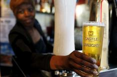 A bartender serves a beer produced by brewing company SAB Miller at a bar in Cape Town, September 16, 2015. REUTERS/Mike Hutchings