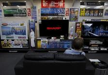 A man sitting on a sofa looks at a Sharp Corp's Aquos TV at an electronics retailer in Tokyo, Japan, June 23, 2015. REUTERS/Yuya Shino