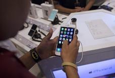 Мужчина изучает iPhone 6 Plus в магазине электроники в Мумбаи 23 июля 2015 года. Американская Apple Inc вынуждена искать и удалять из своего магазина приложений App Store вредоносные программы после первой серьезной атаки на эту платформу. REUTERS/Danish Siddiqui