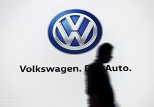 Un hombre camina junto al logo de Volkswagen, en un evento de la compañía en Nueva Delhi, India, 23 de junio de 2015. Las acciones de Volkswagen sufrían su peor baja en casi seis años el lunes luego de que las autoridades estadounidenses acusaron a la automotriz alemana de falsificar datos de emisiones, lo que significa que podría enfrentar penalidades por hasta 18.000 millones de dólares. REUTERS/Anindito Mukherjee