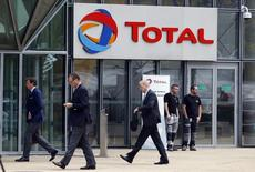People walk past the entrance of French oil giant Total headquarters in the financial and business district of la Defense in Courbevoie near Paris October 21, 2014.  REUTERS/Charles Platiau