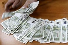 Женщина считает деньги в Национальном банке Грузии в Тбилиси. 31 декабря 2008 года. Глава Центробанка Грузии не ожидает дальнейшего давления на национальную валюту лари после ее укрепления благодаря интервенции центробанка на валютном рынке. REUTERS/David Mdzinarishvili