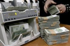 Женщина пересчитывает купюры в ЦБ Грузии в Тбилиси 31 декабря 2008 года. Центробанк Грузии в среду повысил ключевую ставку до 7 процентов с 6-ти в попытке сохранить финансовую стабильность, удержать под контролем инфляцию и поддержать национальную валюту. REUTERS/David Mdzinarishvili