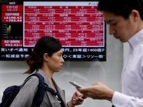 Peatones caminan junto a un tablero electrónico que muestra el índice de precios de varias acciones afuera de una correduría en Tokio, Japón, 9 de septiembre de 2015. El índice Nikkei de la bolsa de Tokio cayó el jueves a un mínimo en más de dos semanas luego de que los mercados japoneses volvieron a abrir tras un feriado nacional de tres días para enfrentar las noticias de una débil actividad fabril en China y Estados Unidos, lo que perjudicó en especial a las acciones de las firmas de maquinaria. REUTERS/Yuya Shino