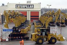 Trabajadores caminan junto a excavadoras en la fábrica de Caterpillar, en Gosselies, Bélgica, 28 de febrero de 2013. Caterpillar redujo en 1.000 millones de dólares sus previsiones de ingresos en el 2015 y dijo que podría recortar hasta 10.000 puestos de trabajo al 2018, en medio de una desaceleración en las industrias minera y energética. REUTERS/Eric Vidal
