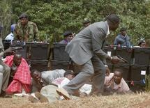 Policemen and civilians take cover around ballot boxes as police used tear gas and shoot with live ammunition during a protest after vote counting was discontinued over poll violence in Kajiado North constituency, near Nairobi December 28, 2007.  REUTERS/Thomas Mukoya