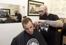 Hugo 'Juice' Tandron gives a haircut to Miami Marlins starting pitcher Jose Fernandez in his barber shop in Marlins Park in Miami, Florida, September 23, 2015.  REUTERS/Joe Skipper