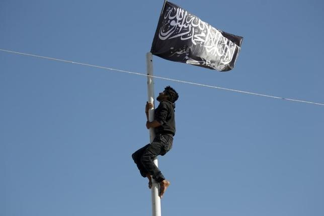 A member of al Qaeda's Nusra Front climbs a pole where a Nusra flag was raised at a central square in the northwestern city of Ariha, after a coalition of insurgent groups seized the area in Idlib province May 29, 2015. REUTERS/Khalil Ashawi