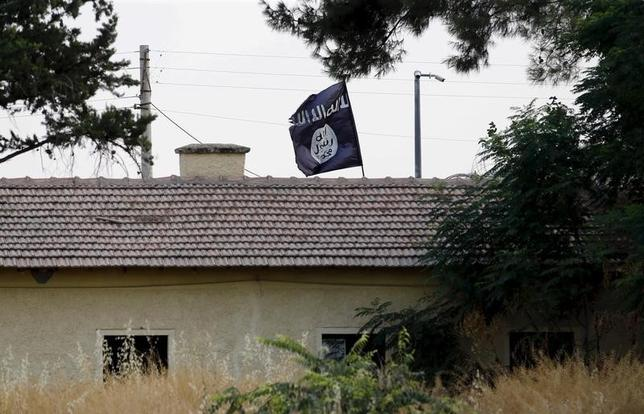 An Islamic State flag flies over the custom office of Syria's Jarablus border gate as it is pictured from the Turkish town of Karkamis, in Gaziantep province, Turkey, August 1, 2015. REUTERS/Murad Sezer