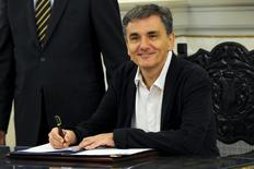 Newly appointed Greek Finance Minister Euclid Tsakalotos signs official documents following a swearing-in ceremony at the presidential palace in Athens, Greece, September 23, 2015.  REUTERS/Michalis Karagiannis