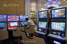 A worker cleans a slot machine inside a new casino following the completion of the second phrase of construction at the Galaxy Macau resort in Macau, China May 27, 2015. REUTERS/Tyrone Siu