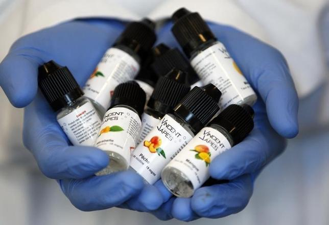 An employee displays e-liquids phials with mirabelle (plum) and mango aromas for electronic cigarettes produced at the ''Vincent dans les Vapes'' factory in Pessac, near Bordeaux, October 9, 2013. REUTERS/Regis Duvignau