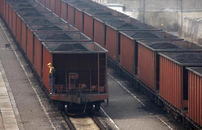 A worker stands on a wagon of a coal train as it tranfers coal to a power plant in Huaibei, Anhui province November 17, 2011. REUTERS/Stringer