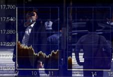 Un hombre se refleja en un tablero que muestra el índice Nikkei, afuera de una correduría en Tokio, Japón, 29 de septiembre de 2015. El índice Nikkei de la bolsa de Tokio rebotó el miércoles, luego de que los inversores hicieron caso omiso a datos que mostraron que la producción fabril de Japón cayó inesperadamente por segundo mes consecutivo en agosto. REUTERS/Issei Kato