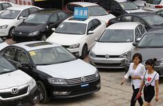 Foto de archivo de unas mujeres caminando delante de unos autos Volkswagen y Honda, en Pekín, 17 de junio de 2014. China recortó a la mitad el impuesto a las ventas de automóviles pequeños para reactivar el crecimiento en el mercado de autos más grande del mundo, una medida que podría dar un impulso limitado a automotrices como Volkswagen AG, envuelta en un escándalo mundial sobre emisiones de diésel. REUTERS/Kim Kyung-Hoon/Files