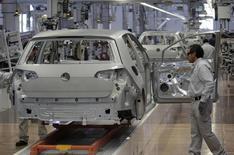 Trabajadores en la línea de ensamblaje de un auto Golf 7, en la planta de Volkswagen en Puebla, México, 14 de enero de 2014. Para los fabricantes de piezas de automóviles en el estado mexicano de Nuevo León, la letra pequeña de un acuerdo comercial del Pacífico que los negociadores esperan concretar esta semana podría preservar o deshacer un auge de la industria exportadora mexicana cuyo valor asciende a 60.000 millones de dólares. REUTERS/Imelda Medina