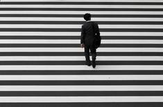 Un trabajador cruza un camino en el distrito financiero de Tokio, 1 de octubre de 2015. La confianza de las grandes compañías manufactureras de Japón se debilitó en los tres meses hasta septiembre y las empresas se mostraron cautas sobre el panorama, mostró un sondeo del banco central, debido a que sintieron los efectos de la turbulencia en los mercados financieros y la disminución de los envíos a China. REUTERS/Toru Hanai