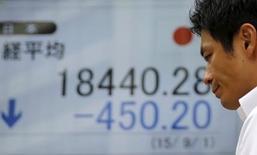 Un hombre camina delante de un tablero electrónico que muestra el índice Nikkei de Japón, afuera de una correduría en Tokio, 1 de septiembre de 2015. Las bolsas de Asia subían el viernes y parecían encaminadas a cerrar la semana con un alza, aunque el panorama sigue siendo sombrío por unas expectativas de crecimiento débil. REUTERS/Toru Hanai