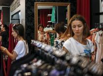 Женщины в магазине одежды в Киеве. 16 июля 2015 года. Темпы инфляции на Украине замедлились в сентябре 2015 года до 51,9 процента в годовом выражении с 52,8 процента в августе, сообщила Государственная служба статистики. REUTERS/Gleb Garanich