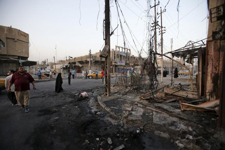 People gather at the site of a car bomb attack in the Ameen district of eastern Baghdad, Iraq, September 22, 2015.  REUTERS/Thaier al-Sudani