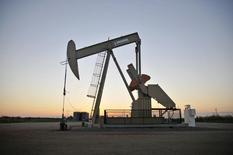 Una unidad de bombeo de crudo de la firma Devon Energy Production Company operando cerca de Guthrie, EEUU, sep 15, 2015. Los precios del petróleo cayeron el miércoles en una sesión volátil, cortando un repunte de tres jornadas después de que los datos oficiales mostraron un gran incremento en los inventarios de crudo de Estados Unidos, algo que sorprendió a los inversores un día después de un informe que indicó lo contrario.     REUTERS/Nick Oxford