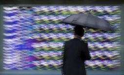 Un hombre mira un tablero electrónico que muestra la información de las acciones, afuera de una correduría en Tokio, 8 de septiembre de 2015. Las acciones chinas se ponían al día con un repunte mundial luego de un receso de una semana y subían con fuerza en una sesión donde la mayoría de los mercados de Asia perdía terreno. REUTERS/Issei Kato