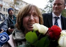 Belarussian author Svetlana Alexievich holds flowers as she arrives to attend a news conference in Minsk, Belarus, October 8, 2015. REUTERS/Vasily Fedosenko