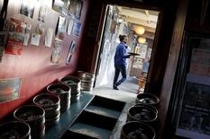 Una mujer lleva una cerveza producida por SABMiller, en un bar en Ciudad del Cabo, 16 de septiembre de 2015. La cervecera SABMiller, que intenta evitar una oferta informal de compra de su rival Anheuser-Busch InBev, anunció un acelerado plan de ahorro de costos el viernes en un intento por convencer a los accionistas de que puede impulsar las ganancias por su cuenta. REUTERS/Mike Hutchings