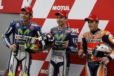 Yamaha MotoGP rider Jorge Lorenzo (C) of Spain poses with Yamaha MotoGP rider Valentino Rossi (L) of Italy and Honda MotoGP rider Marc Marquez of Spain after winning the pole position for Sunday's Japanese Grand Prix after a qualifying session at the Twin Ring Motegi circuit in Motegi, north of Tokyo, Japan, October 10, 2015.  REUTERS/Issei Kato