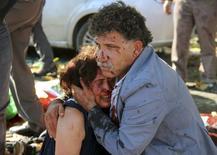 Раненные в результате взрыва мужчина и женщина в Анкаре 10 октября 2015 года. По меньшей мере 20 человек погибли в результате взрывов, прогремевших у вокзала в столице Турции Анкаре в субботу, сообщило новостное агентство Dogan. REUTERS/Tumay Berkin